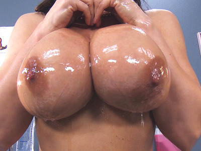 Lisa Ann pours a lot of oil all over her astonishing boobs
