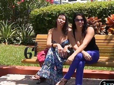 两个性感的女人炫耀他们的大胸部一些钱
