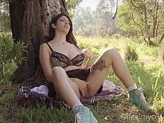 Busty teen masturbates by a tree
