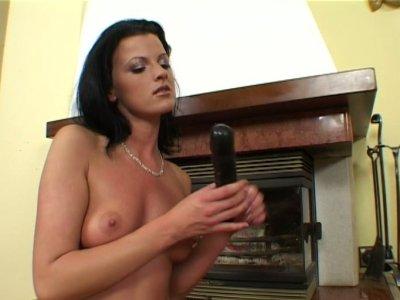 Shiny brunette seductress Juditta treats her twat with black stick
